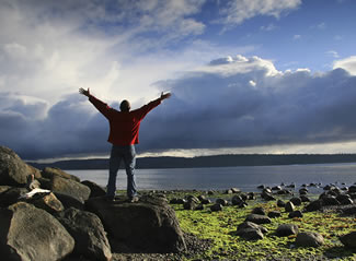 Photo of a man holding his arms up in front of a lake.