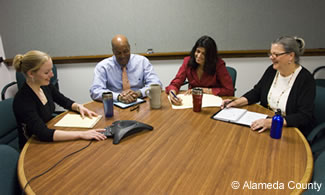 Photo of 4 County employees conducting a teleconference.